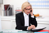 彼女のオフィスでの携帯電話上の女性 — ストック写真