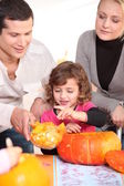 Family carving hallowe'en pumpkin — Stock Photo