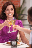 Two female friends drinking champagne in restaurant — Stock Photo