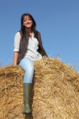 Female cultivator posing on hay bale — Stock Photo