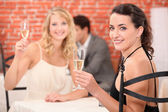 Two girls dressed in robes toasting in a restaurant — Stock Photo