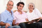 Grandparents and grandson skimming through album — Stock Photo