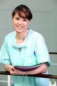 Nurse in scrubs holding files — Stock Photo