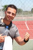 Male tennis player with bottle of water and towel — Stock Photo