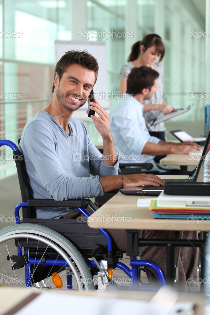 Smiling man in a wheelchair working in an office  Stock Photo #7230366