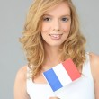 Pretty young woman holding a French flag — Stock Photo