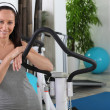 Woman standing next to an exercise machine — Stock Photo