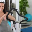 Stock Photo: Woman standing next to an exercise machine