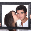 Girl tenderly kissing a man on the cheek behind black frame — Stock Photo