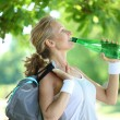 Stock Photo: Sporty woman drinking water from a bottle