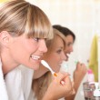 Three young ladies brushing their teeth — Stock Photo