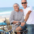 Senior couple riding bikes on the beach — Stock Photo