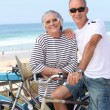 Stock Photo: Senior couple riding bikes on the beach