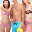Three friends stood on a beach — Stockfoto