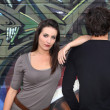 Couple hanging out by wall painted with graffiti — Stock Photo #7362876
