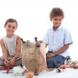 Children playing with plastic toy figurines — Stock Photo
