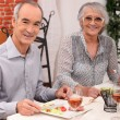 Old couple eating at a restaurant — Stock Photo