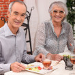 Old couple eating at a restaurant - Stock Photo