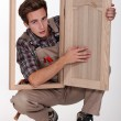 A young carpenter showing a piece of furniture - Stock Photo