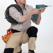 Tradesman holding up an electric screwdriver — Stock Photo #7365355
