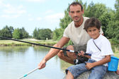 Father and son on a fishing trip at a lake — Stock Photo