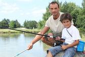 Vader en zoon op een visreis aan een meer — Stockfoto