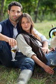 Couple having bottle of wine in field — Stock Photo