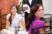 Two women drinking sparkling wine at restaurant — Stock Photo