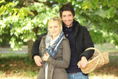 Young couple behind trees in autumn, man holding a wickerwork basket — Stock Photo
