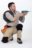 Tradesman holding up an electric screwdriver — Stock Photo