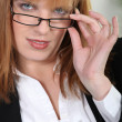 Royalty-Free Stock Photo: Businesswoman peering over her glasses