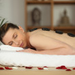 Laid woman having hot stones massage — Stock Photo