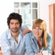 Couple having a coffee in a kitchen - Stock Photo