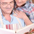 Smiling man and woman selecting recipe on a cookbook — Stock Photo