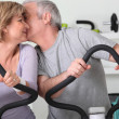 Man and woman on cross trainers kissing — Stock Photo #7373591