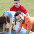 Young doing press ups in the park — Stock Photo