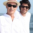 Father and son sat by waterfront — Stock Photo
