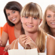 Three female friends at home with shopping bags — Stock Photo