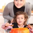 Mother and daughter carving jack-o-lanterns — Stock Photo #7374571