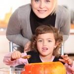 mor och dotter som snida jack-o-lyktor — Stockfoto