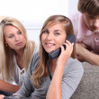 Stock Photo: Three teenagers making telephone call