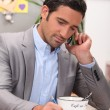 Businessman working at the breakfast table - Stock Photo