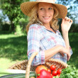 Woman with a straw hat and basket of vegetables. — Stock Photo