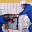 Two plumber working in public rest room - Stock Photo
