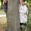 Couple standing behind a tree trunk - Stock Photo