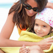 Mother drying daughter with towel at the beach — Stock fotografie