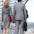 Business couple arriving at airport - Stock Photo
