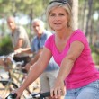 Woman riding a bike with friends in a forest — Stock Photo #7376058
