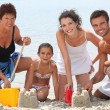 Family building sandcastles on the beach - Stok fotoğraf