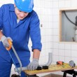 Stock Photo: Plumber sawing plastic pipe
